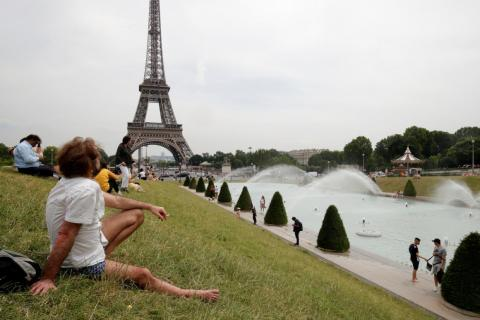 People sunbathe near the Trocadero fountains and the Eiffel tower in Paris as a heatwave is expected in much of the country on Monday.