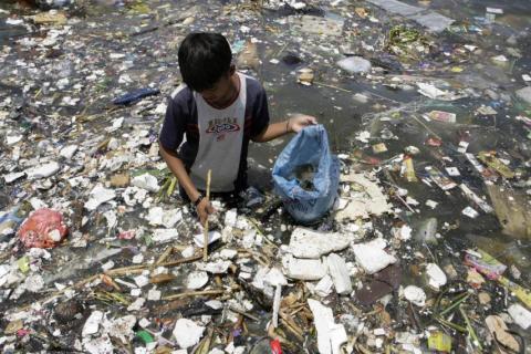 Un niño filipino recoge materiales plásticos cerca de una costa contaminada para venderlos en Manila.