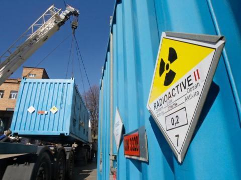Trabajadores colocan un contenedor con uranio altamente enriquecido en un camión en una instalación de investigación nuclear en Kiev el 24 de marzo de 2012.