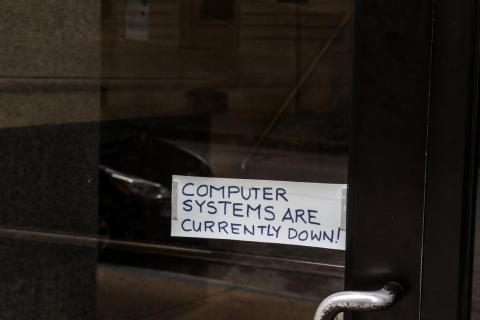 A sign referring to the hacked computer system of Baltimore City is taped to a door near Baltimore City Hall in Baltimore, Maryland, in May 2019.