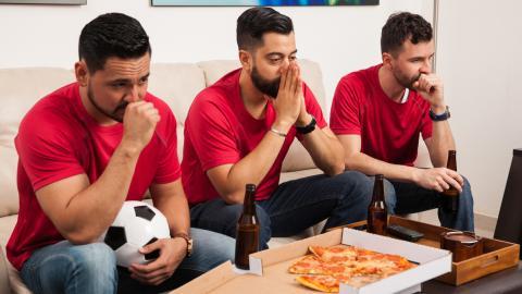 Tres amigos ven en casa un partido de fútbol.