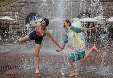 Unas niñas juegan en una fuente con chorros de agua en Kiev.