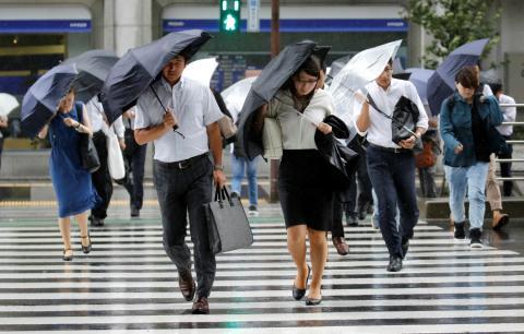 Unas personas cruzan un paso de cebra mientras se protegen del peligro de la lluvia con un paraguas.