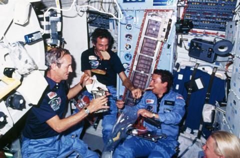 Los astronautas comen a bordo del transbordador espacial Discovery.