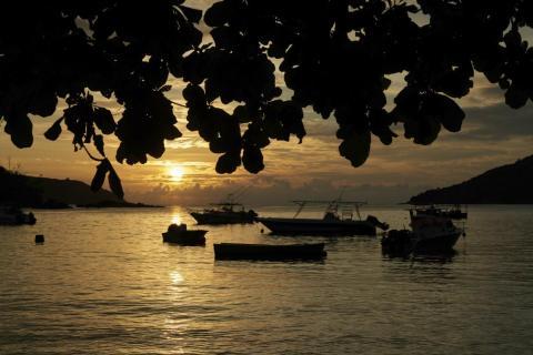 El sol se pone sobre una pequeña bahía pesquera con embarcaciones de recreo cerca de la isla de Mahe, Seychelles.