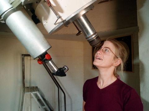 Una astrónoma mirando por un telescopio