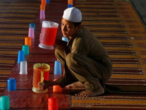 Un niño prepara jarras de zumo para que los musulmanes rompan su ayuno durante el Ramadán en un punto de distribución gratuita de alimentos en Rawalpindi, Pakistán, el domingo 20 de mayo de 2018.