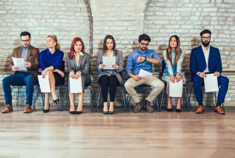 Candidatos esperando antes de una entrevista de trabajo con un currículum vitae en sus manos