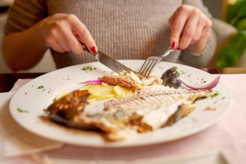Chica comiendo pescado