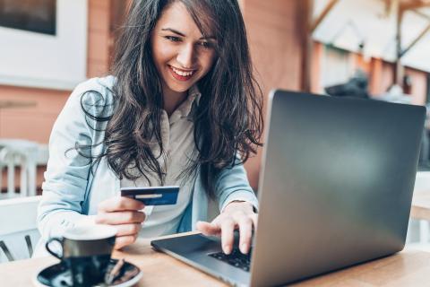 Una chica utiliza una tarjeta de crédito para hacer compras online.