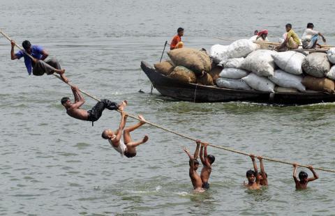 Los bangladesíes se aferran a una cuerda mientras se zambullen en el río Buriganga para refrescarse del calor del verano en Dhaka, el 16 de mayo de 2005.