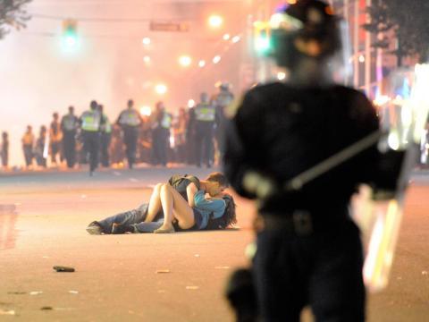Besos en la calle mientras la policía antidisturbios trata de disolver un disturbio en Vancouver, Canadá.