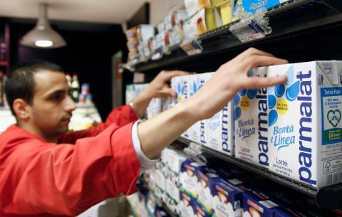 Un dependiente coloca cartones de leche Parmalat en un supermercado