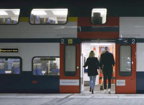 Dos personas suben a un tren en Lausana (Suiza)
