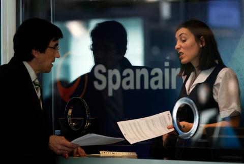 Una empleada de Spanair habla con un pasajero