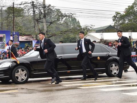 Guardaespaldas norcoreanos corriendo junto a una limusina que lleva al líder de Corea del Norte, Kim Jong Un, a su llegada a la ciudad fronteriza con China en Dong Dang, Vietnam, el 26 de febrero de 2019