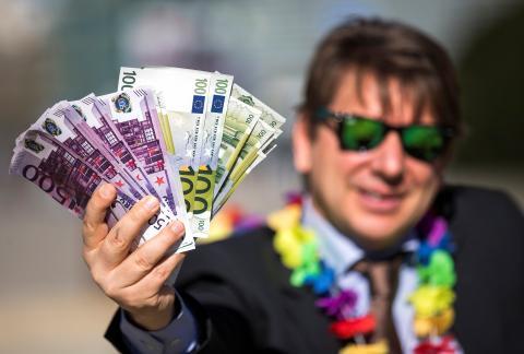 Un hombre sostiene un fajo de billetes de euro