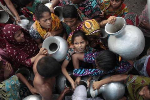 28 de mayo de 2012. Un grupo de personas se empujan mientras sostienen ollas de agua para recogerla de un camión de la Autoridad de Agua y Alcantarillado (WASA) en las afueras de Dhaka.