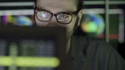 Un joven frente a un monitor de ordenador.