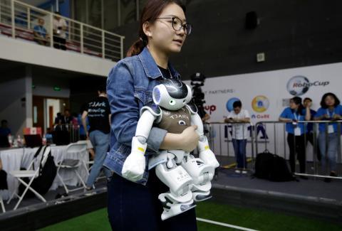 Una joven lleva un robot en una competición de robots.
