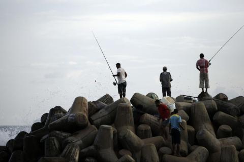 Maldivos pescan desde una pared de mar cuando las olas lo golpean en Malé, Maldivas.