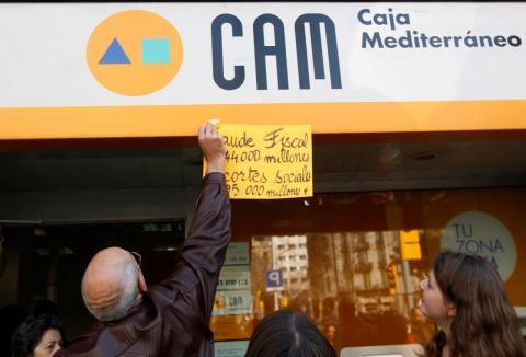 Unos manifestantes protestan ante una sucursal de la CAM