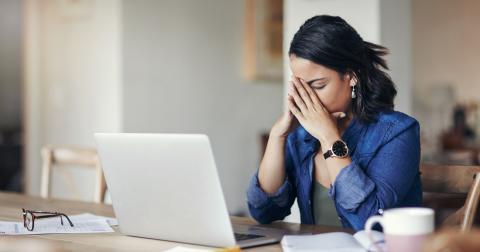Mujer con las manos en la cabeza frente al ordenador