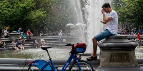 La gente se refresca cerca de la fuente en Washington Square Park durante un día caluroso de la tarde del 17 de julio de 2019 en la ciudad de Nueva York.
