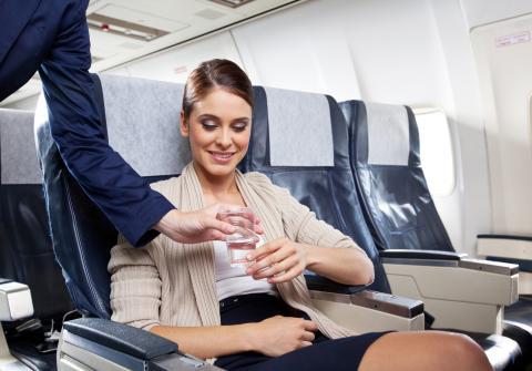 Una persona bebe agua en un avión.