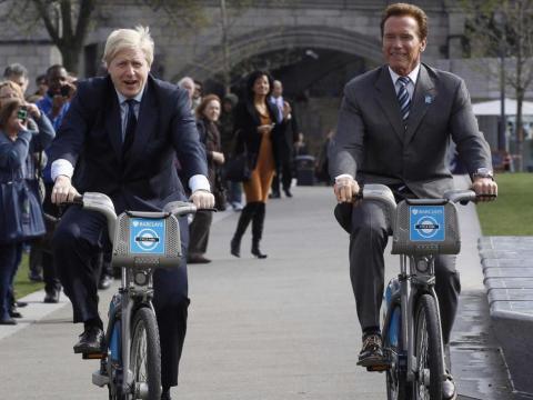 """El plan de bicicletas de la ciudad lleva por nombre no oficial """"bicicletas Boris"""". Aquí ves a Johnson disfrutando mientras monta al lado de Arnold Schwarzenegger."""