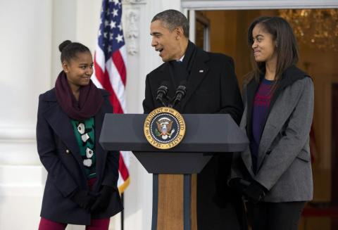 """President Barack Obama, with daughters Sasha, left, and Malia, makes a joke during remarks at the Thanksgiving tradition of saving a turkey from the dinner table with a """"presidential pardon,"""" at the White House in November 2013."""
