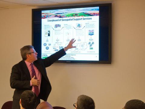 Un científico de información geoespacial dirigiendo una presentación.