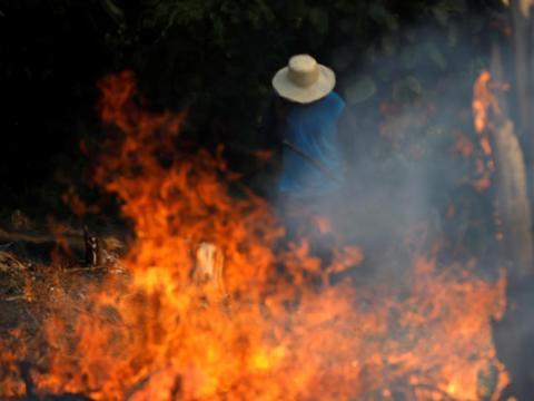 Un hombre trabaja en una zona en llamas de la selva amazónica mientras los madereros y agricultores de Iranduba, estado de Amazonas, la limpian.