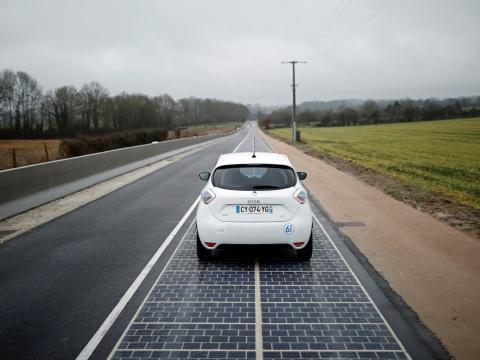 Un automóvil circula por la carretera de paneles solares.