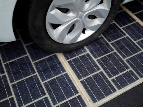 Los neumáticos de un automóvil sobre una carretera con paneles solares.