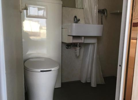 The bathroom features a toilet and a sink, as shown below.