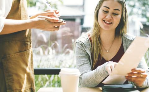 Una chica pide en un restaurante con la carta en la mano.