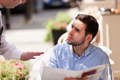 Un chico pide en una terraza de un restaurante.
