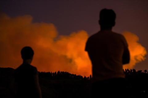 Dos personas contemplan el humo de un incendio forestal en Valleseco, en la isla de Gran Canaria.