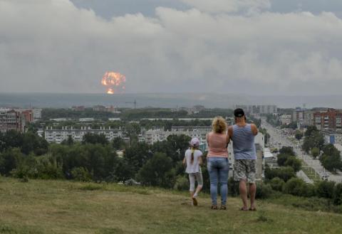 Una familia observa explosiones en un depósito de municiones militares cerca de Achinsk, Rusia, el 5 de agosto. Funcionarios rusos dicen que estas explosiones dejaron 12 heridos y un desaparecido y obligaron a más de 16.500 personas a irse.