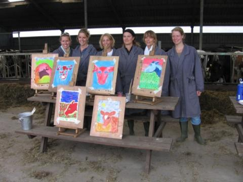 Un grupo de mujeres posa con sus pinturas después de una terapia con vacas