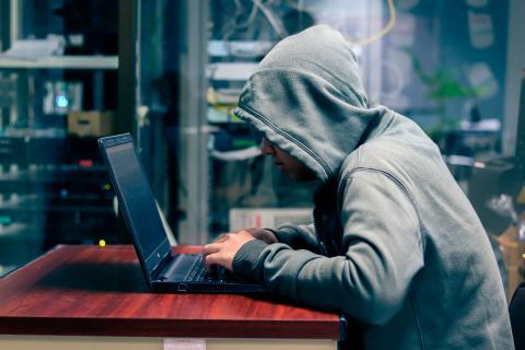 Un hacker frente a la pantalla de un ordenador portátil