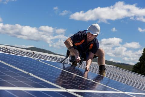 Hombre instalando paneles solares en el tejado