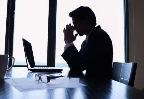 Hombre pensativo en sombras mirando un ordenador