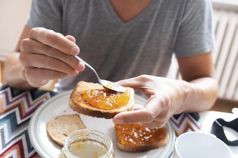 Hombre untando mermelada en una tostada