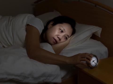 Mujer en la cama mirando el despertador