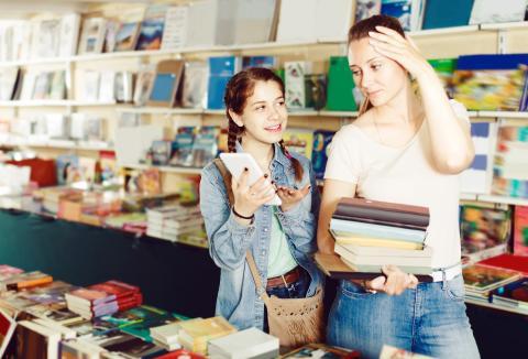 Madre e hija comprando libros de texto para el colegio