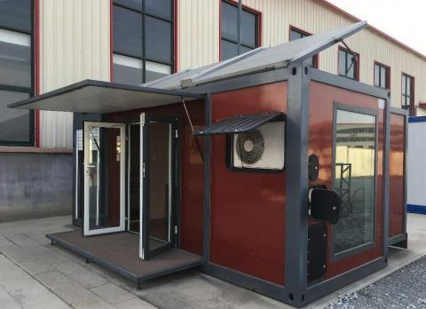 The module container house expands with a remote control. It features a folding deck and canopy, and solar panels can be seen on the roof.