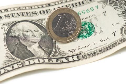 Moneda de un euro sobre billete de un dólar