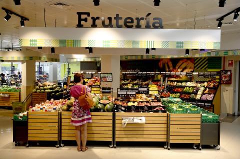 Una mujer mira la fruta en una frutería de un supermercado.